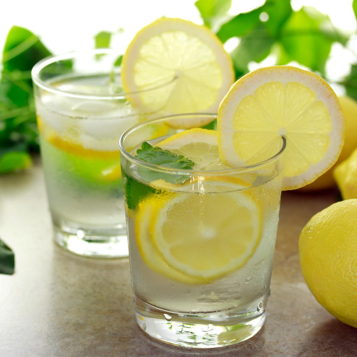 Glass of water with lemon slices and herbs